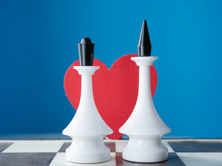 couple marriage wedding invitation idea. two chessman king and queen with red heart behind with blue background