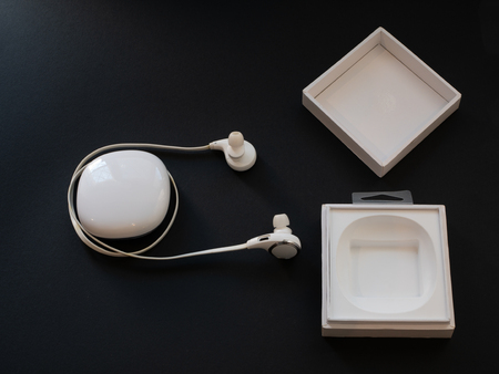 white opened box with wireless in-ear headphones headset on black background. low key image Imagens