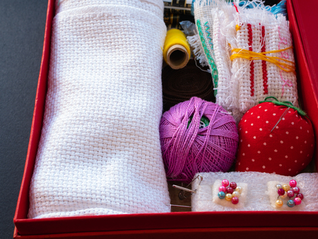 box with needlework equipment like needles, threads, pins, tissue, textile, cloth, fabric for craft handmade