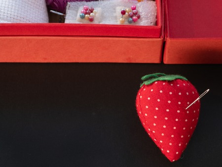 small needle pod in shape of strawberry with box full of needlework equipment on black background