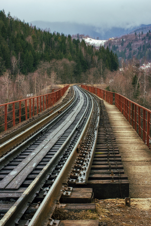 empty railway railroad tracks with old vintage wooden ties sleepers leads from viewer to mountains. way path concept. outdoor spring image. Carpathian Mountains, Ukraine
