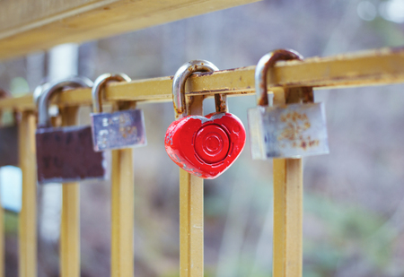 door locks hanging on a metal fence on a bridge of love. selective focus on one padlock in shape of heart red colored as a symbol of romantic affairs
