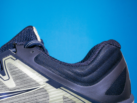 closeup of sport sneakers shoe on blue background. hole where you place your feet Imagens