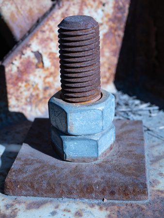 closeup of big rusty industrial bolt screw with nuts which hold in place huge outdoor billboard