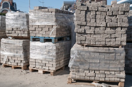 outdoor warehouse with lot of pallets full of bricks pavement stones Imagens