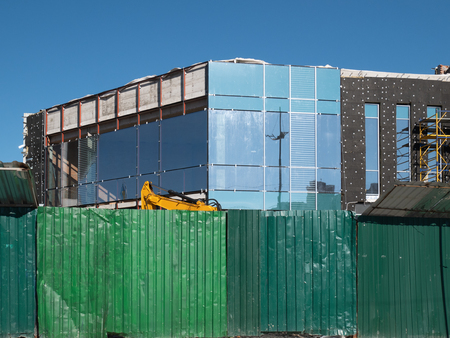 green fence in front of construction site. small office building or townhouse made from glass, metal and concrete Imagens