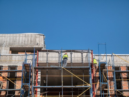 few man workers on scaffolding at construction site of modern office building, store, shopping mall or residential condo