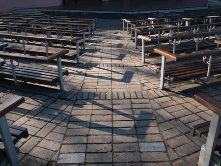 aisle between empty seats rows of wooden benches at open air city park theater. outdoor spring fall autumn image Imagens