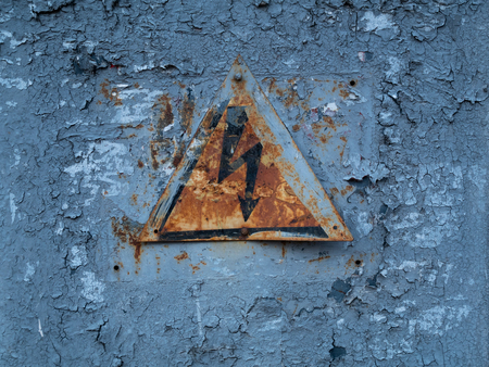 vintage weathered high voltage warning danger sign with lightning on old rusty transformer substation panel