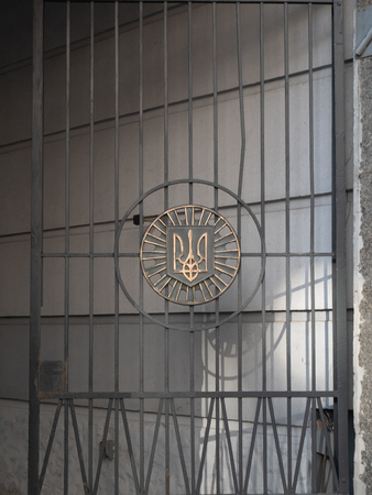 ukrainian trident traditional symbol tryzub - official coat of arms of Ukraine. forged on fence made of steel bars