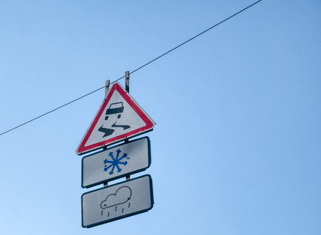 signs of slippery road at rainy or snowy days hanging on wire with clear blue sky as background Imagens