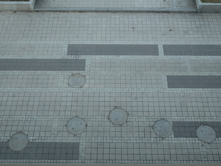 view from top on sidewalk pavement made of concrete tiles with lot of round hatchways