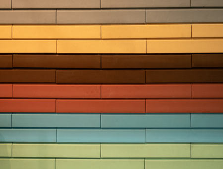 abstract pattern wall made of different colors bricks - orange, red, brown, gray, yellow, blue, green. pastel tones