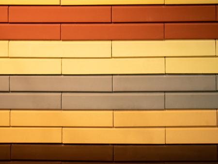 abstract pattern wall made of different colors bricks - orange, red, brown, gray and yellow