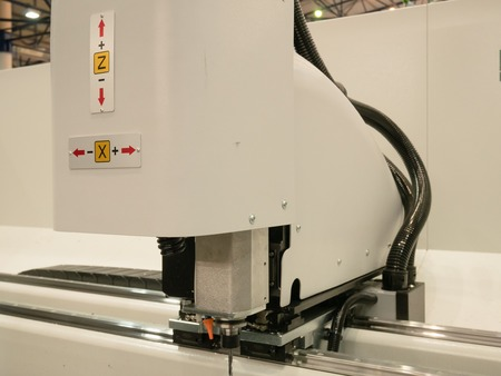 automated industrial programmable laser cutting engraving machine. closeup side view image inside manufacture facility