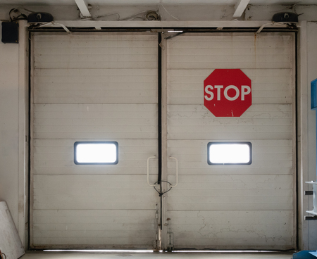 closed automatic gates inside industrial storage warehouse with red stop sign. look from inside storehouse