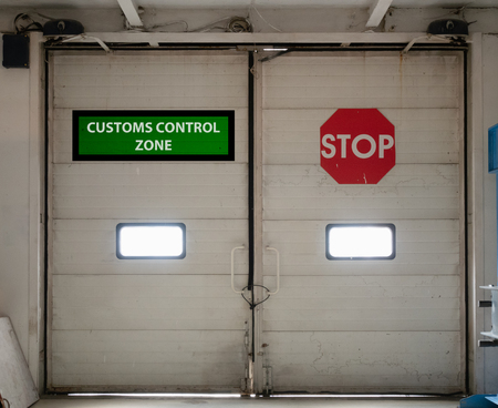 customs control zone automatic gates doors inside security check area with vivid red stop sign. concept of closed border for import or export