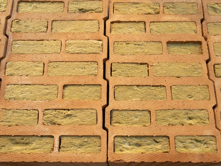 sample of wall made of hollow bricks with mineral wool for insulation of modern development building which help people save money on utility bills with more efficient power consumption.