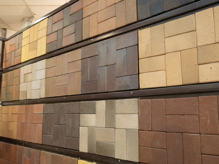 wall made of different samples of sidewalk pavement bricks tiles. various colors and patterns. indoor warehouse image