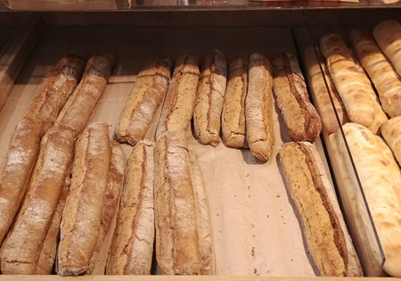 lot of freshly baked hot crisp and delicious baguettes at storefront shelfs made from different types of dough and buckwheat flour