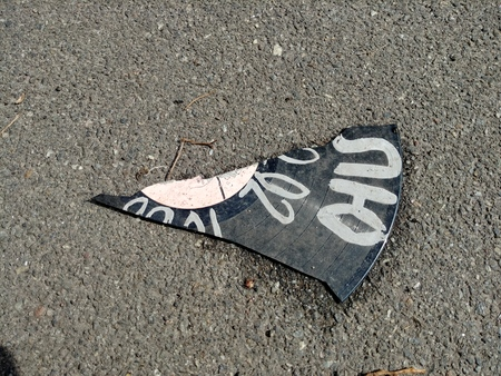 piece of broken vinyl record lay on ground asphalt