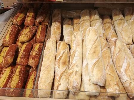 hot freshly baked crisp french baguettes and fancy bread at storefront shelf Imagens