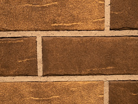 closeup of textured brown brick wall with neat seals between stones Imagens