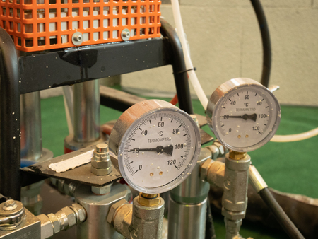 closeup of two analog indicators of temperature with arrows showing current hot or cold condition of liquid paint in automatic pneumatic air pressure equipment, selective focus on closer one Imagens
