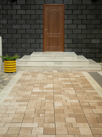 neat pavement porch made of stone tiles leading to modern house entrance door with few marble steps and cute yellow flower pot. strong color contrast between bright sidewalk and dark black wall