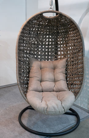 closeup modern armchair in shape of eggshell or birds nest made of woven bamboo, Wicker, Rattan swinging hanging on a stand with grey soft pillow cushion