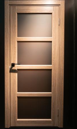 closeup of wooden home room door with few matt glass window frames