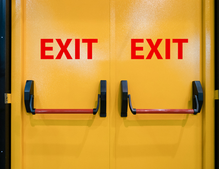 closeup bright vivid yellow double doors for emergency exit Imagens
