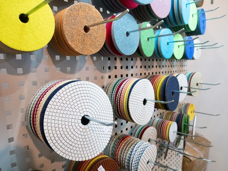closeup many different polishing and grinding replaceable disks for industrial power tools hanging on stand at hardware equipment market