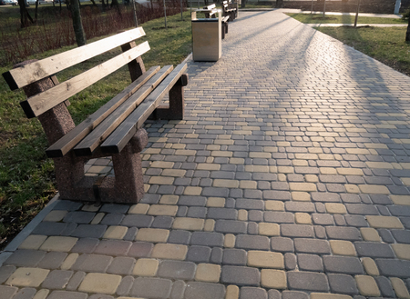 empty alley with bench and cobblestone sidewalk at city park at sunset