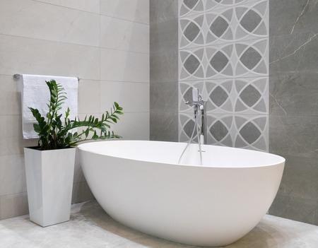 bagno dal design moderno con vasca da bagno in pietra bianca, parete in piastrelle grigie, vaso di fiori in ceramica con pianta verde e appendiabiti con asciugamano