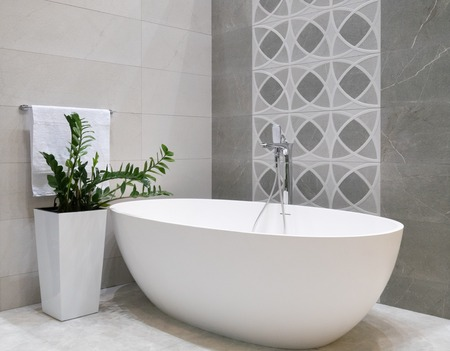 Diseño de interiores de baño moderno con bañera de piedra blanca, pared de azulejos grises, maceta de cerámica con planta verde y percha con toalla