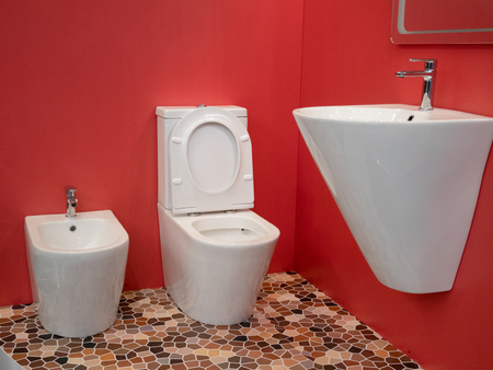 modern home bathroom interior design with white washbasin, toilet, bidet and vivid red walls Imagens - 121187224