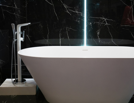 modern white bathtub at hotel apartment with black marble wall on background. contemporary interior design at bathroom