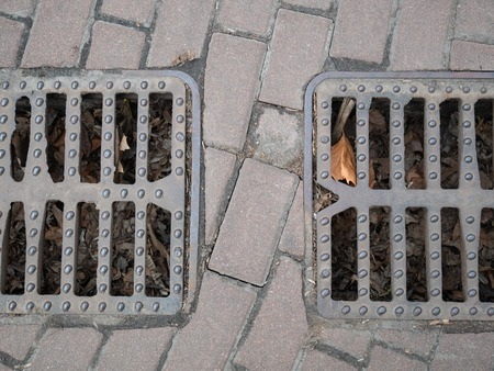two city sewer grids on a pavement for rain water flows to prevent flood