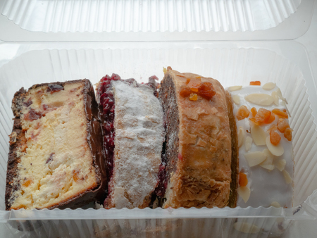 closeup of four pieces of different cakes in transparent plastic disposable container