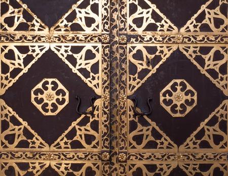 closeup of antique church door with golden ornate Imagens