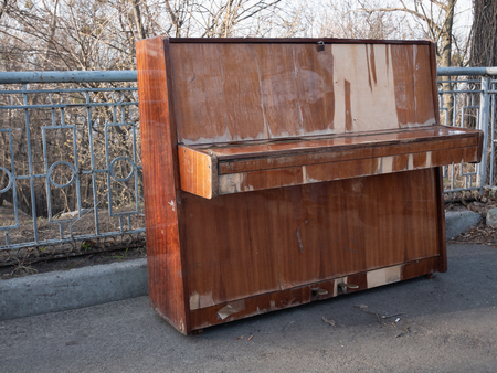 side view on abandoned retro classical wooden piano at city park. concept of open air concert Imagens - 121187383