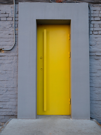bright yellow metallic door in grey wall. entrance to city cafe Imagens