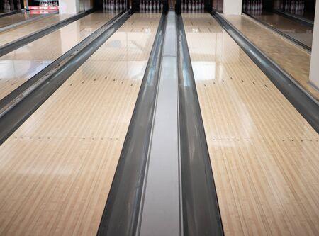 zweispurige Bahnen im Bowlingclub mit einer Reihe von Bowling-Pins in weiter Ferne. Bild mit niedrigem Winkel