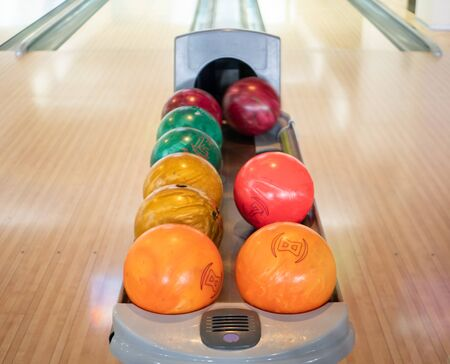 group of colorful balls at bowling club. nobody in the frame. family recreational leisure activity concept. one blurred ball rolling out of black hole Imagens