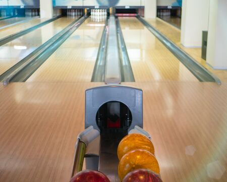 view on two empty lanes tracks at bowling entertainment club and a stand with balls. ready for competition or championship Imagens
