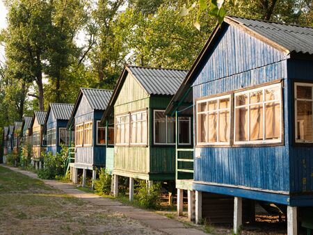 row of old vintage wooden colorful small houses in the woods with weathered peeled painting Zdjęcie Seryjne