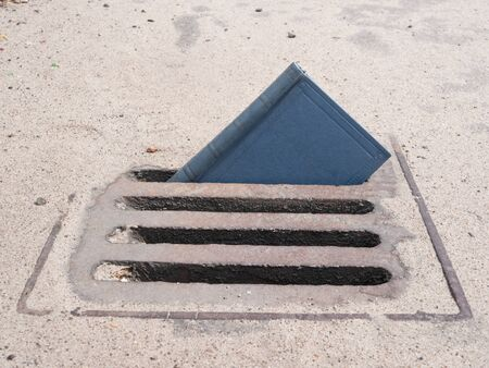 small paper book sticking out from rain drainage. low quality education concept