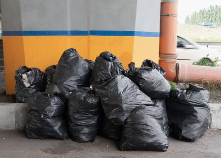heap of black trash bags on city street waiting for delivery to recycle plant. waste recycling concept