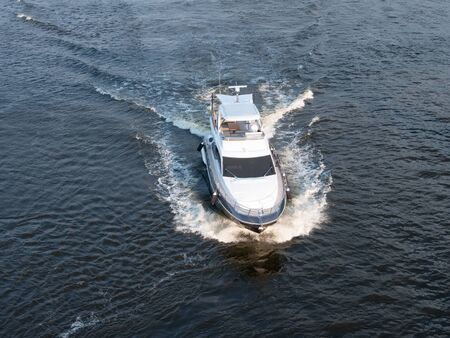 aerial drone shot of small motorized luxury white yacht sailing at the sea towards viewer. image from above
